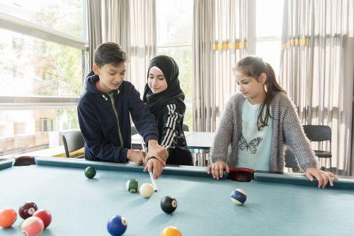 Zwei Schülerinnen und ein Schüler unterschiedlicher Herkunft spielen Billard