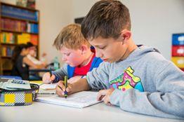 Mehrere Schülerinnen und Schüler erledigen schriftliche Aufgaben.