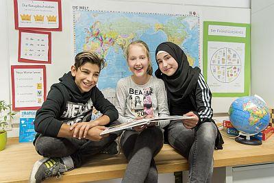 Zwei Schülerinnen und ein Schüler unterschiedlicher Herkunft sitzen mit Buch vor einer Weltkarte
